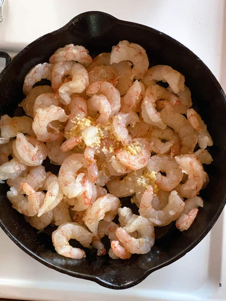 Raw shrimp with minced garlic in cast iron skillet.