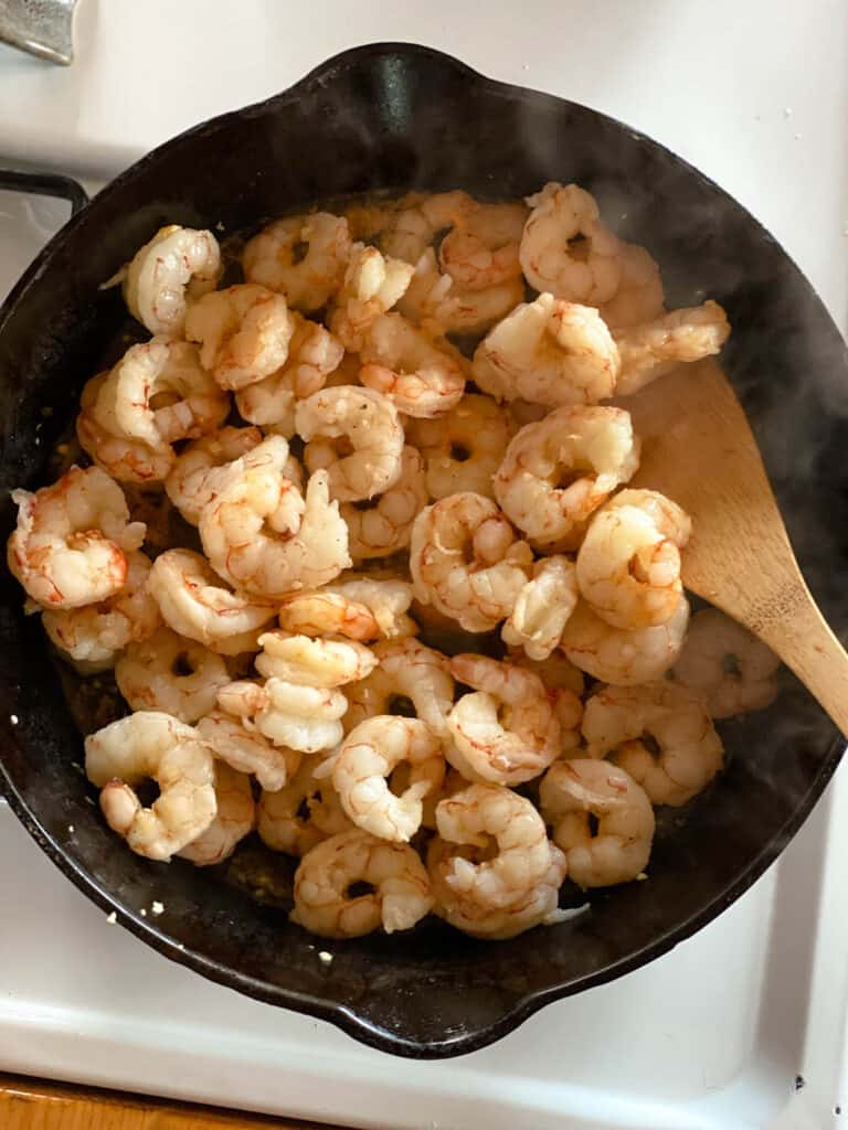 Cooked shrimp in cast iron skillet with wooden spatula.
