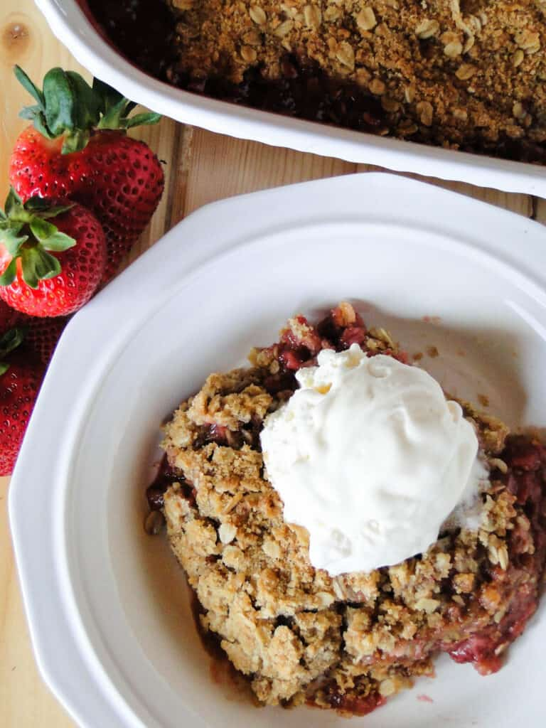 Top view of easy strawberry rhubarb crisp in white bowl next to dish with ice cream on top.