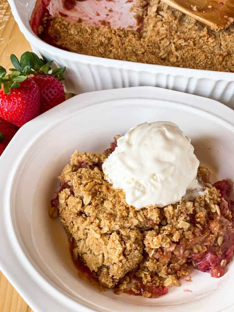 Side view of easy strawberry rhubarb crisp in white bowl in front of full baking dish.