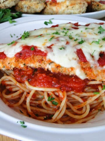 Baked chicken parmesan on a bed of spaghetti in white round pasta bowl.