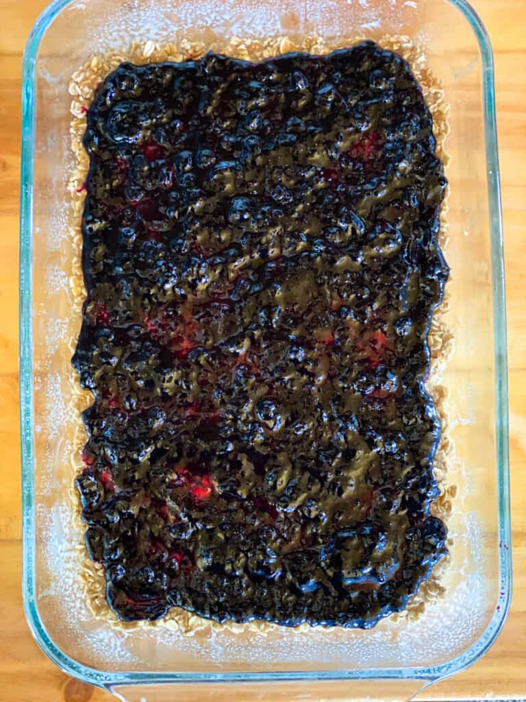 Blueberry jam spread out into even layer on dough.