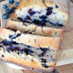 Loaf of blueberry sweet bread with 3 slices in front.