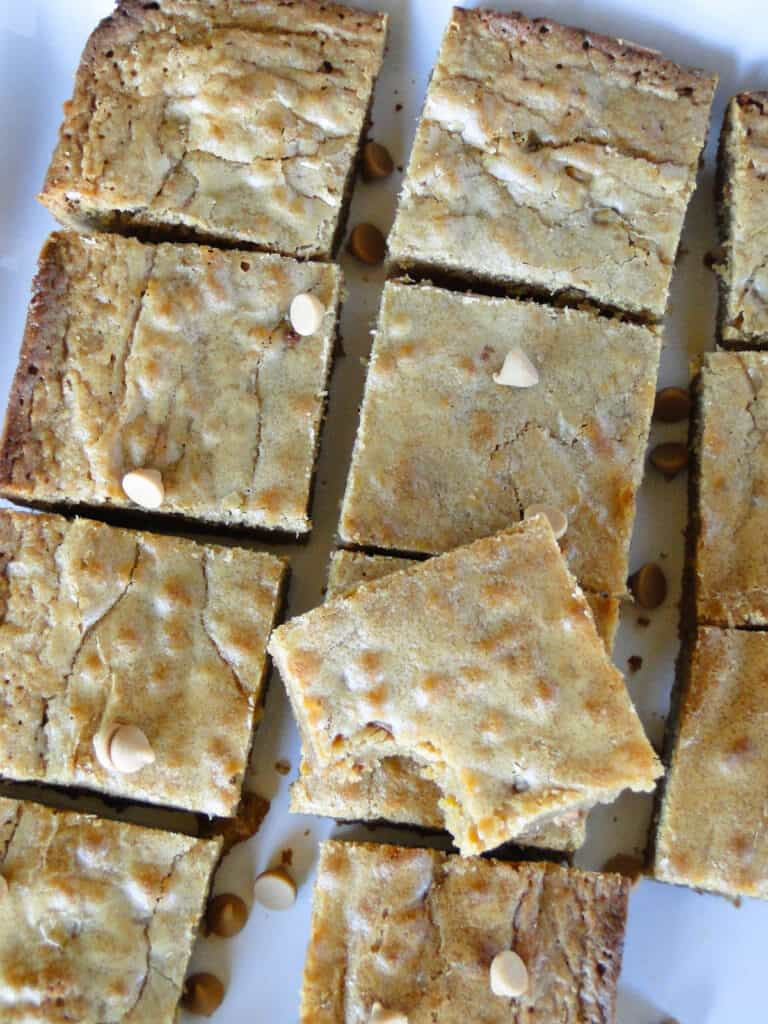 Top view of butterscotch blondies cut into squares with bite taken out of one bar sitting on top.
