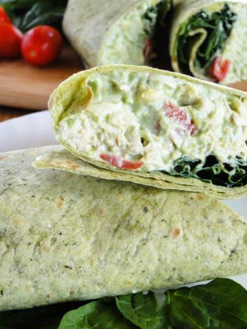 Chicken avocado salad cut in half on white round plate.