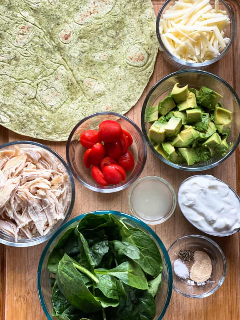 Chicken avocado wraps ingredients on board.