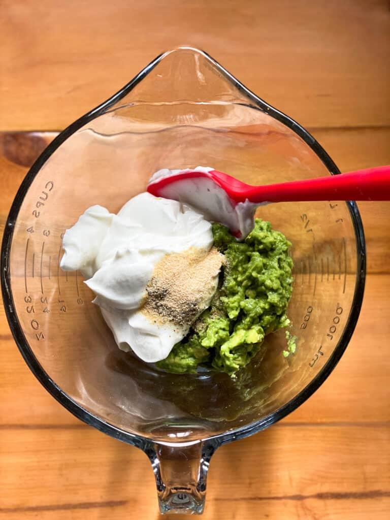 Smashed avocados in bowl with greek yogurt and seasonings in bowl.