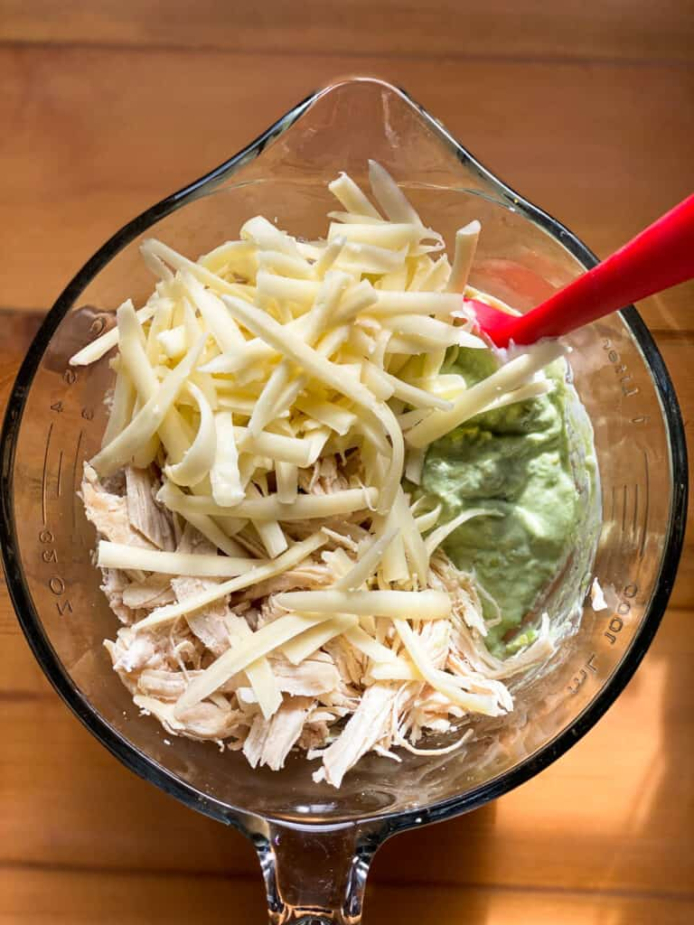 Chicken and shredded cheese added to avocado and yogurt mix.