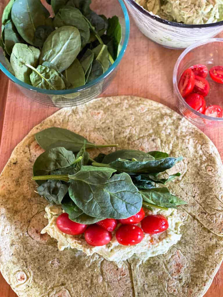 Chicken avocado salad topped with grape tomatoes and spinach on tortilla.