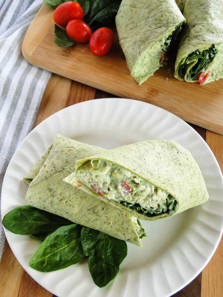 Top views of chicken avocado wraps cut in half on white round plate.
