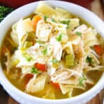Classic chicken noodle soup in white bowl.