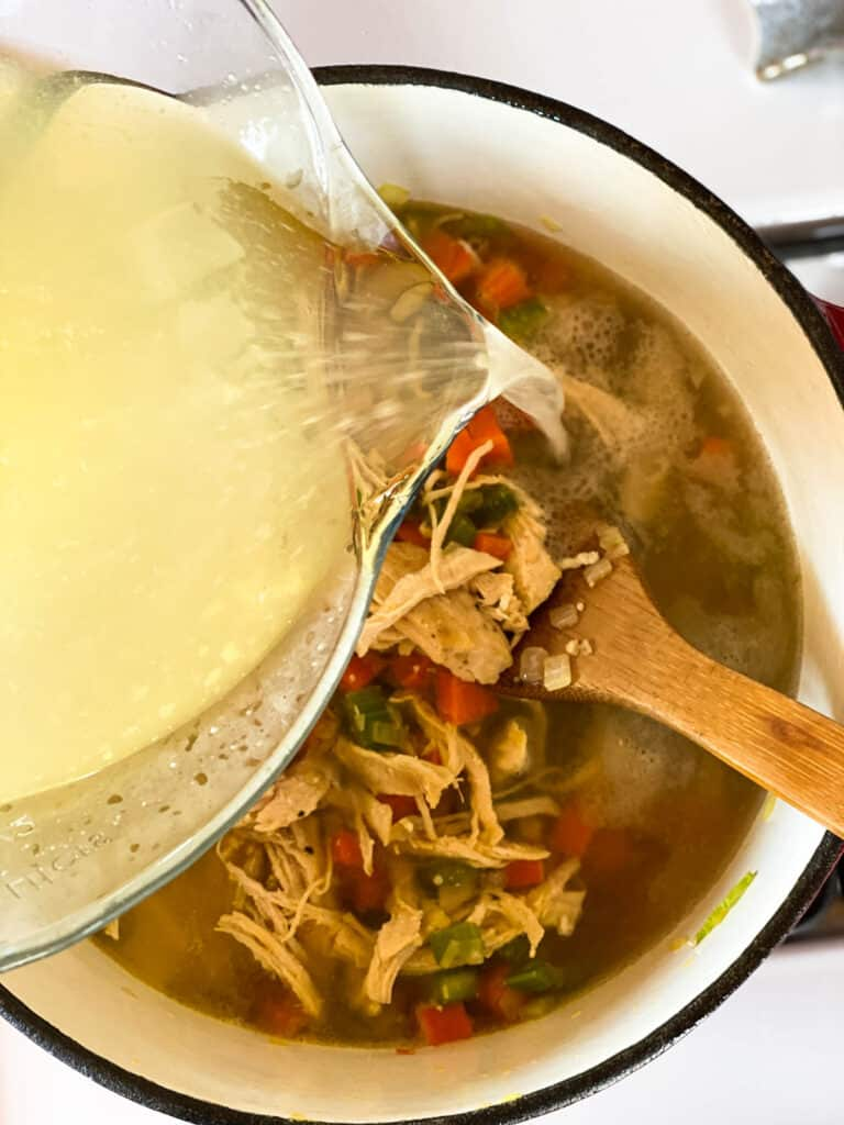 Chicken broth being poured into dutch oven with chicken and vegetables.