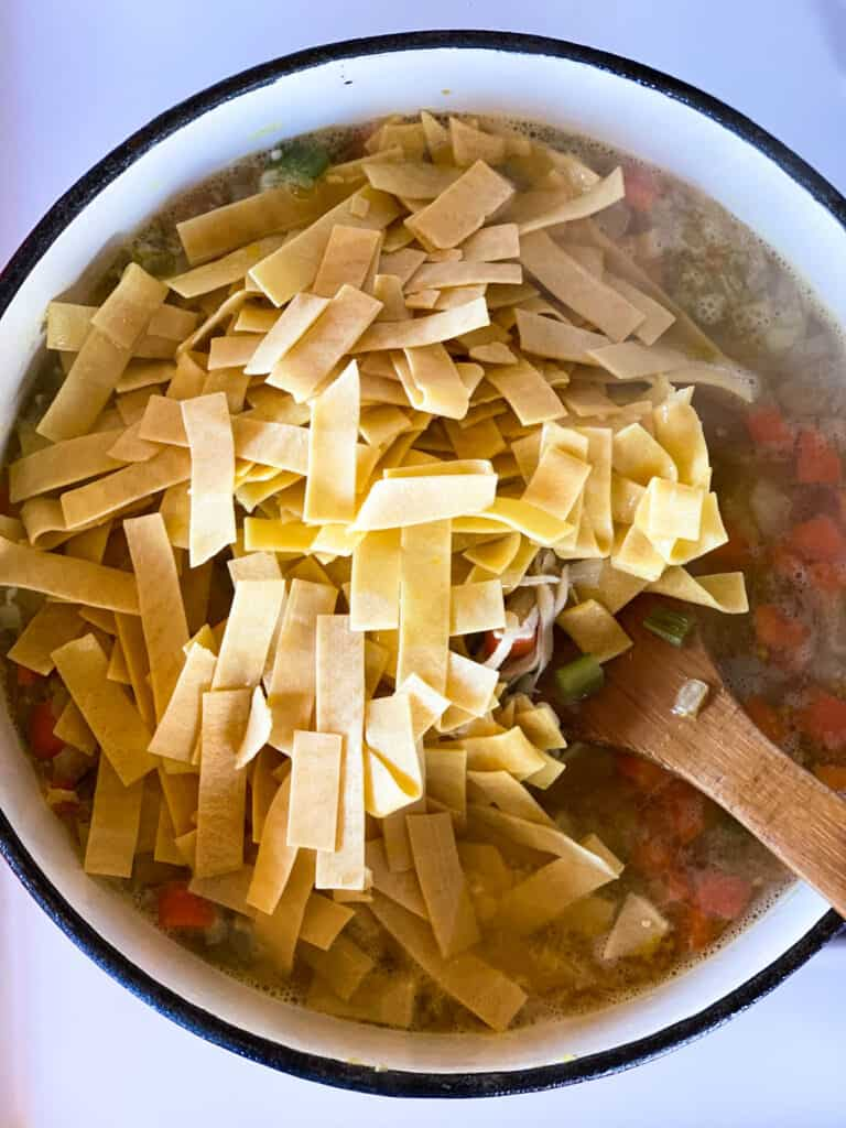 Egg noodles added to simmering chicken soup.