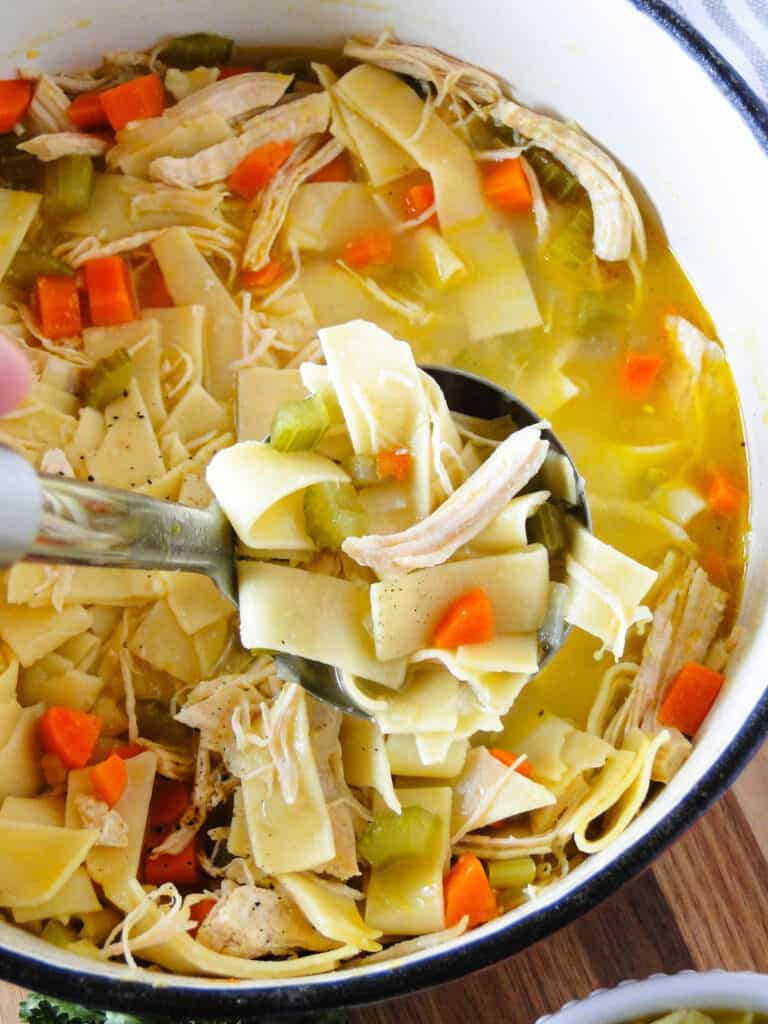 Dutch oven full of chicken noodle soup with a ladleful.