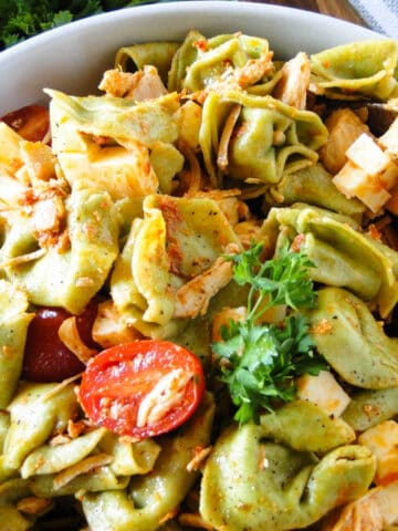 Chicken tortellini salad with wood serving spoon in bowl.
