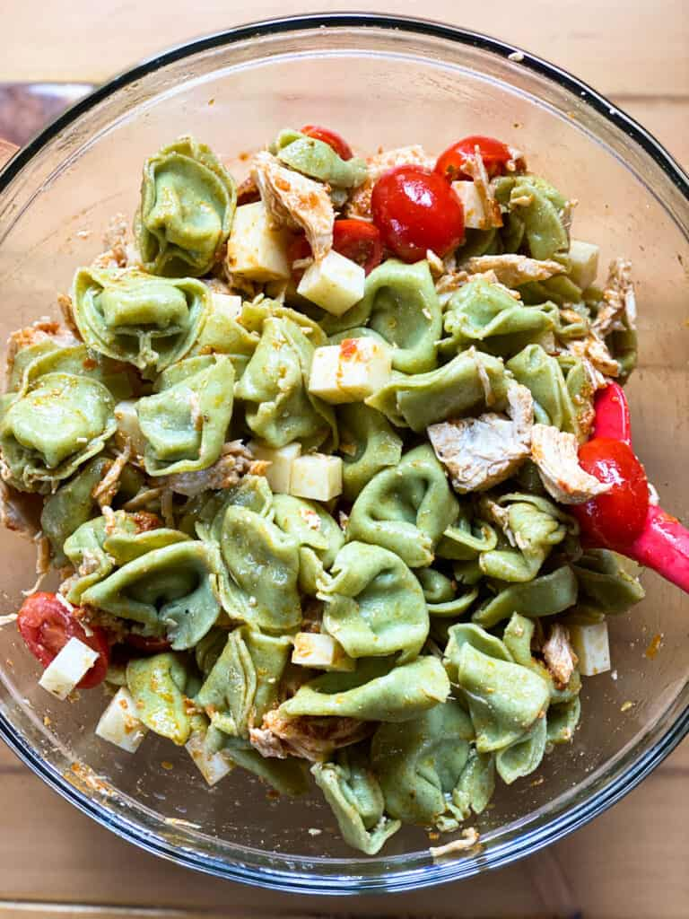All ingredient for chicken tortellini salad tossed together in glass bowl.