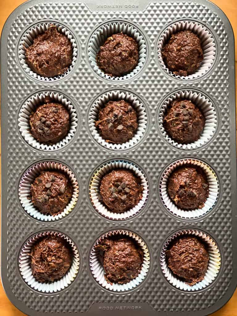 Muffin batter scooped into paper lined muffin pan.