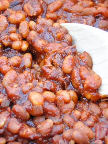Crock pot baked beans with wooden spoon.