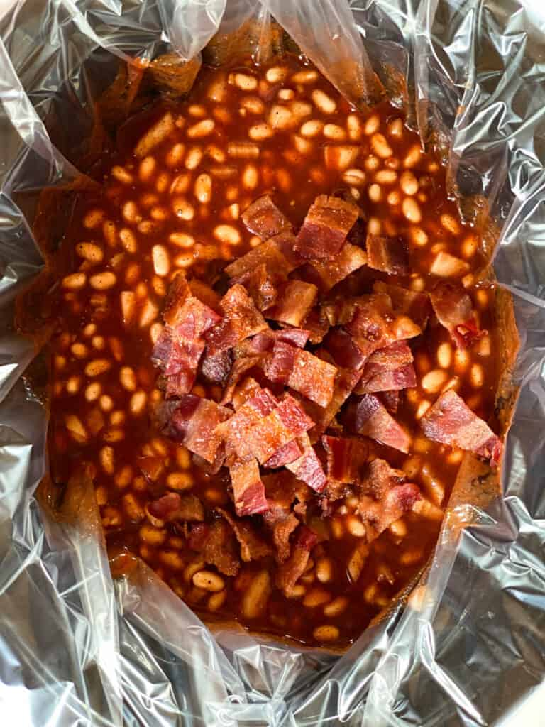 Sauce and beans in crock pot with bacon added.
