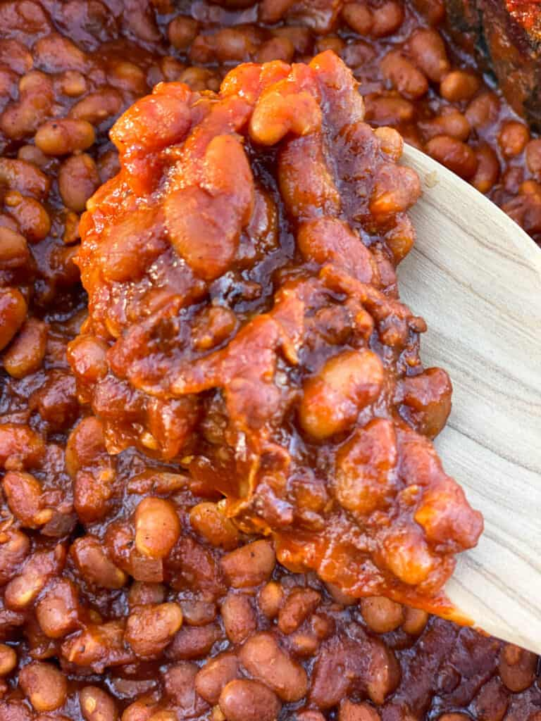Spoonful of crock pot baked beans on wooden spoon.