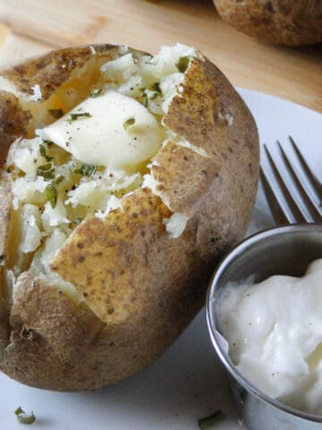 Instant pot baked potato on white round plate with pat of butter and parsley on top and side of sour cream on plate with a fork.
