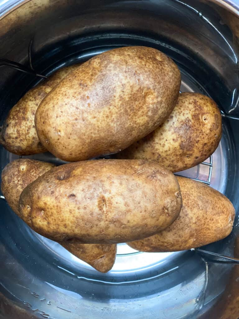 Potatoes stacked in instant pot ready to be cooked.