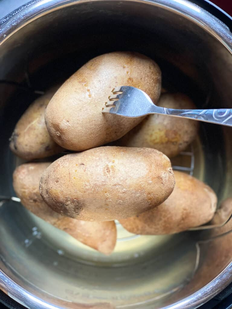Potatoes are fork tender, with a fork in the potato.