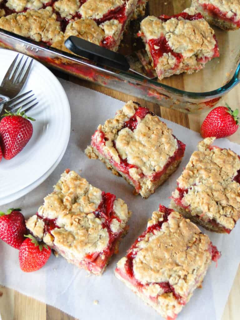 Top view of sliced strawberry rhubarb bars on parchment paper in front of baking dish.