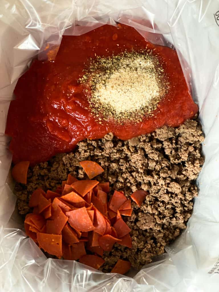 Cooked beef in crock pot with tomatoes, pepperoni and seasonings.