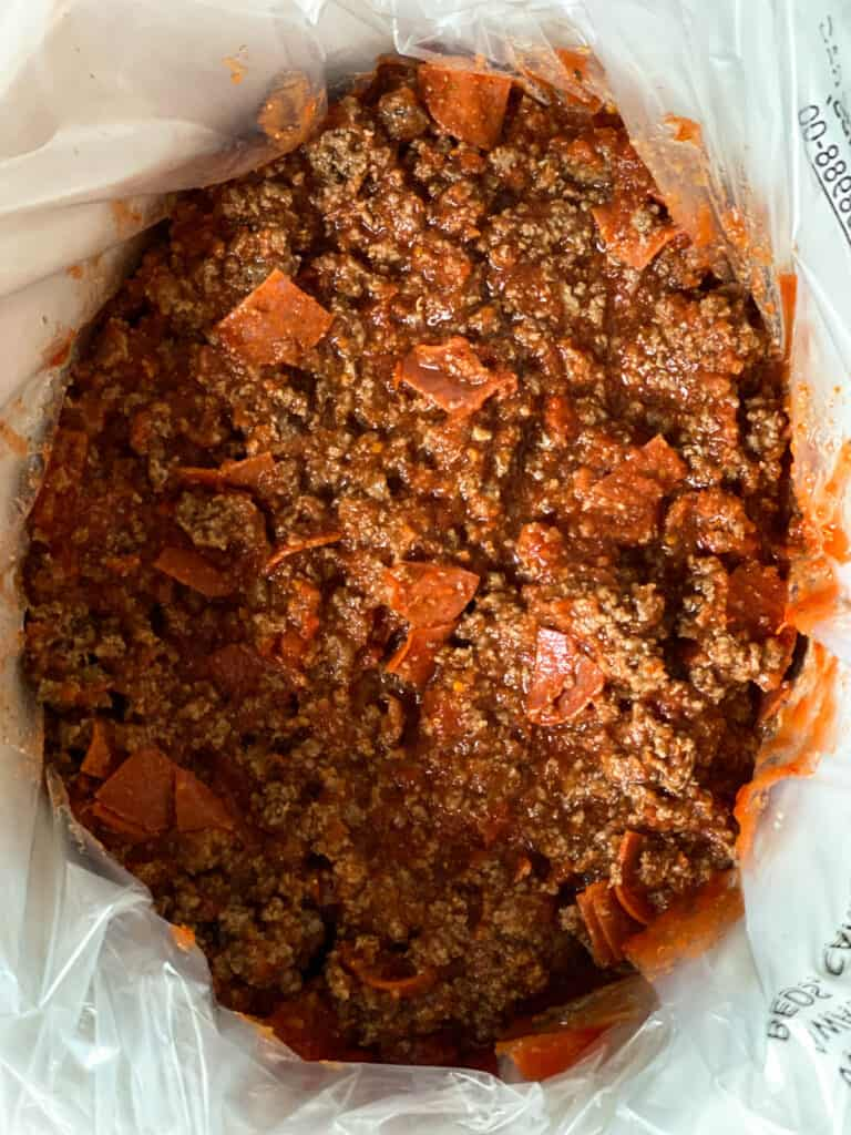 Cooked beef fully combined with tomatoes, chopped pepperonis and seasonings in crock pot.
