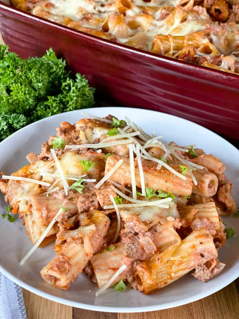 Baked rigatoni casserole on white round plate in front of red casserole dish.