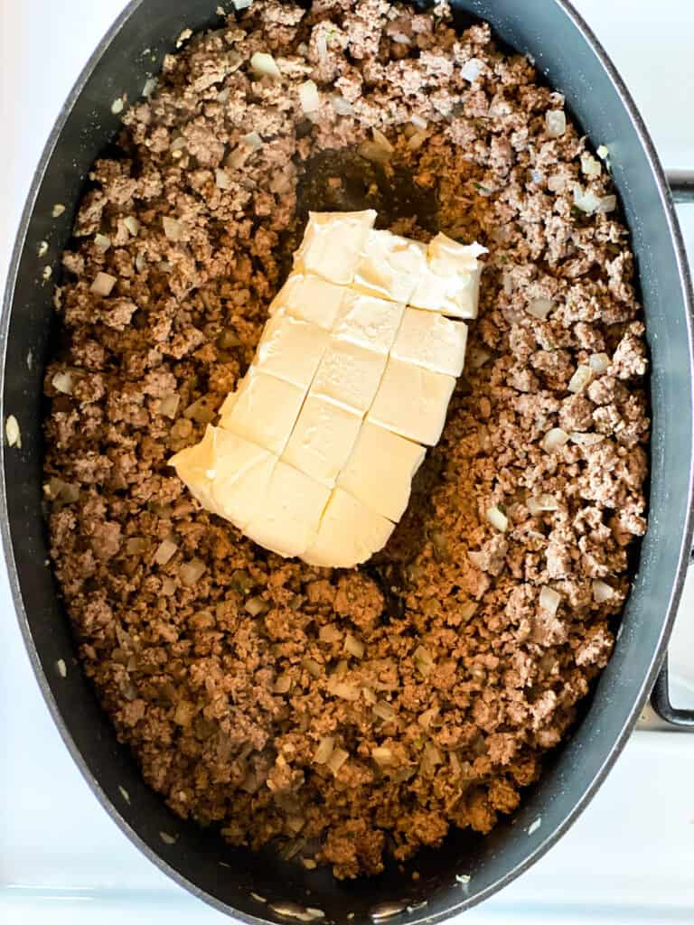 Cubed cream cheese added to cooked and seasoned ground beef.