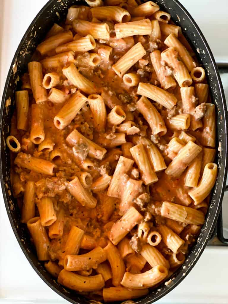 Cooked rigatoni pasta added to the cheesy meat sauce.