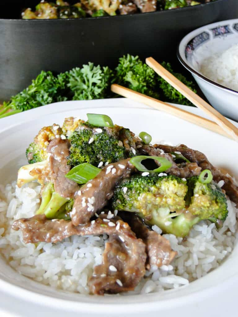 White bowl of rice topped with beef and broccoli stir fry and garnished with sesame seeds and green onions with chop sticks.