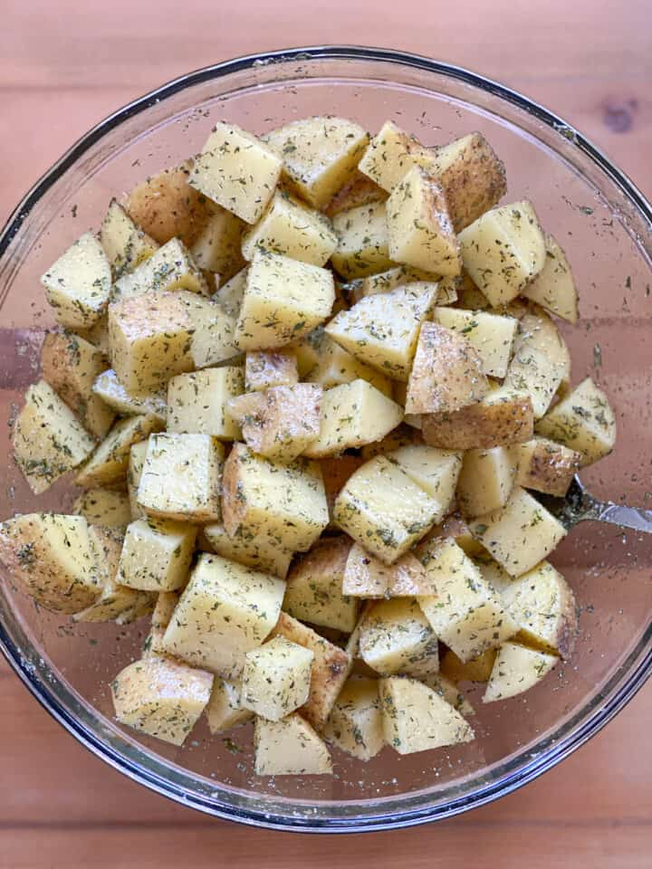 Cut potatoes mixed with ranch seasoning in large glass bowl.