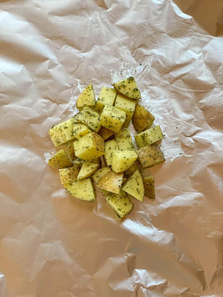 Potatoes piled on aluminum foil.