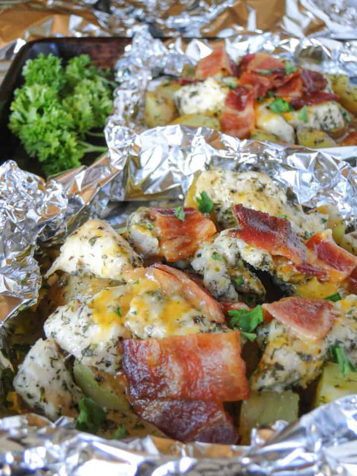 Chicken bacon ranch foil packets opened on a sheet pan.