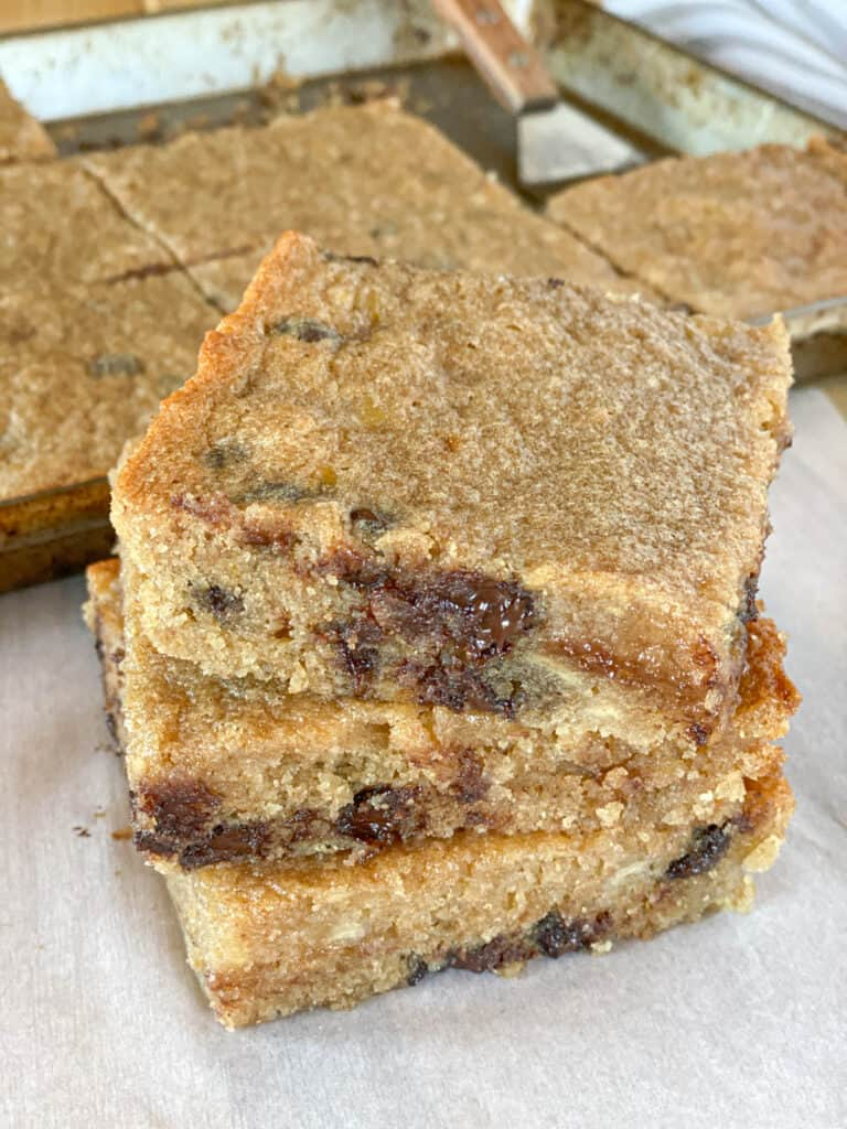 Chocolate chip banana blondies sliced and stacked 3 high in front of pan of bars.