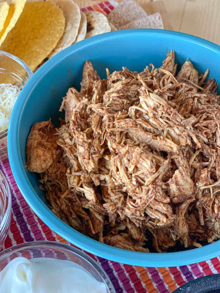 Close view of shredded taco seasoned chicken in blue bowl.