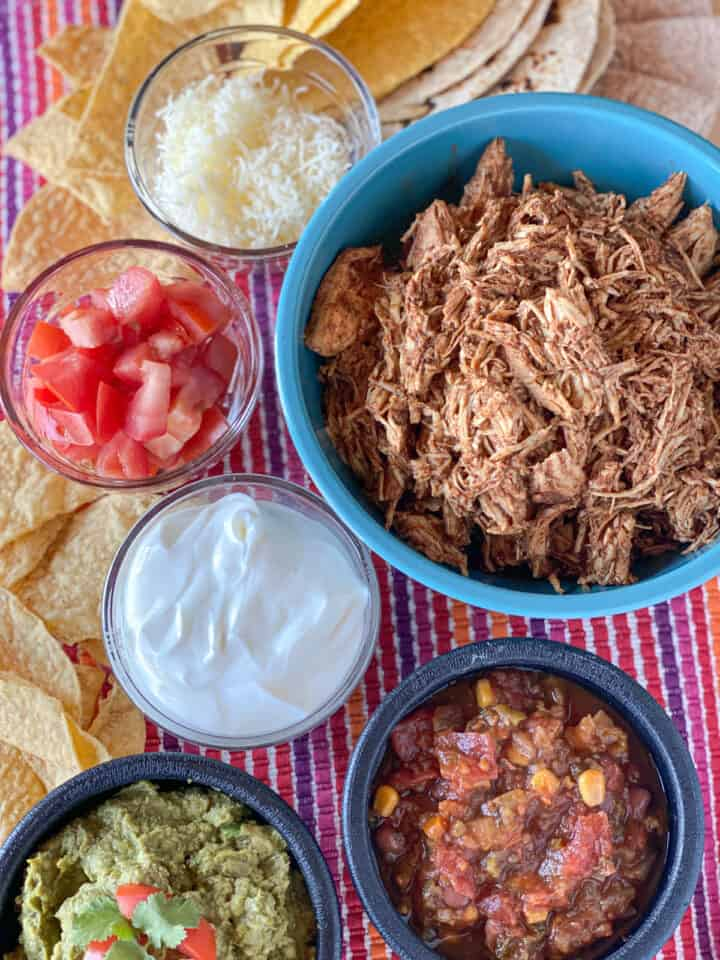 Top view of crock pot chicken taco meat in blue bowl surround by taco toppings.