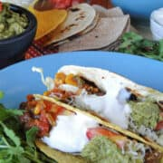 Crock pot chicken tacos with all the fixings on round blue plate.