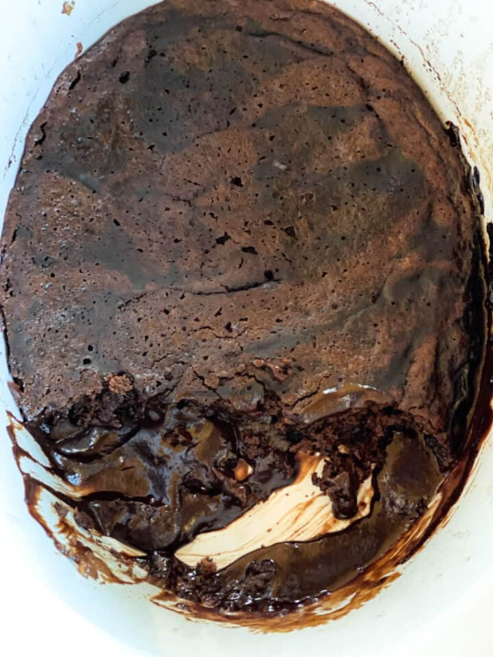 Crock chocolate lava cake in crock pot with some dished out showing pudding like bottom of cake.