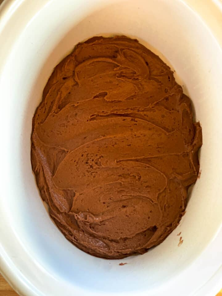 Cake batter spread into bottom of crock pot.