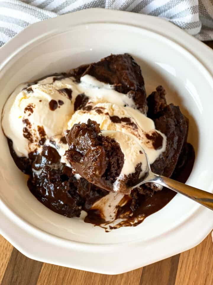 Large spoonful of crock pot chocolate lava cake served in a white bowl topped with vanilla ice cream.