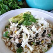 Crock pot cilantro lime chicken served over rice in a white bowl topped with shredded cheese, greek yogurt, sliced avocados, and fresh cilantro.