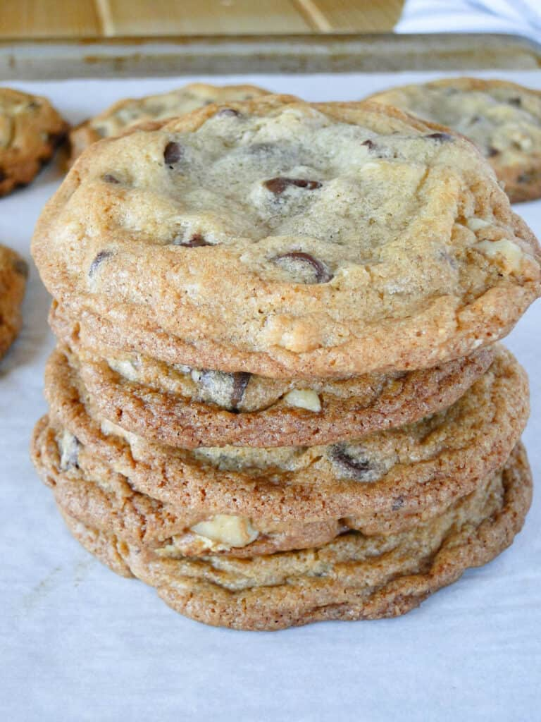 Jumbo chocolate chip cookies stacked 4 high on cookie sheet.