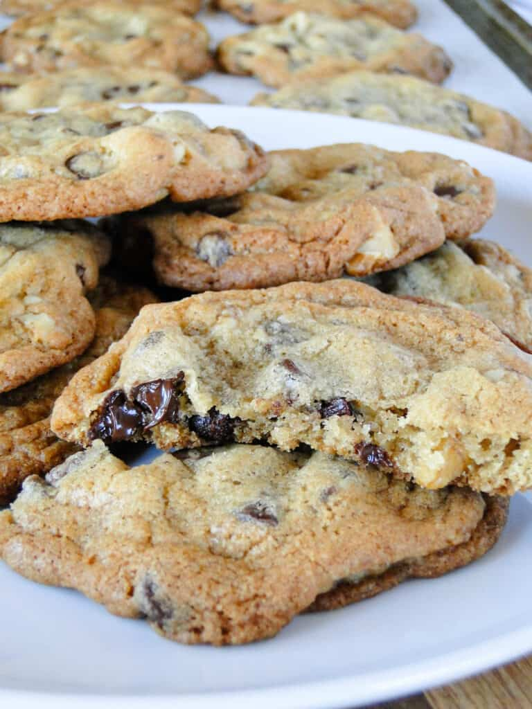 Jumbo chocolate chip cookies piled on plate with one cookie broke in half showing the chewy center.