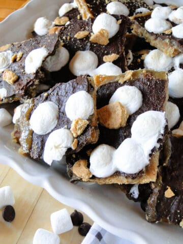 Close up view of broken pieces of s'mores cracker toffee on white platter.