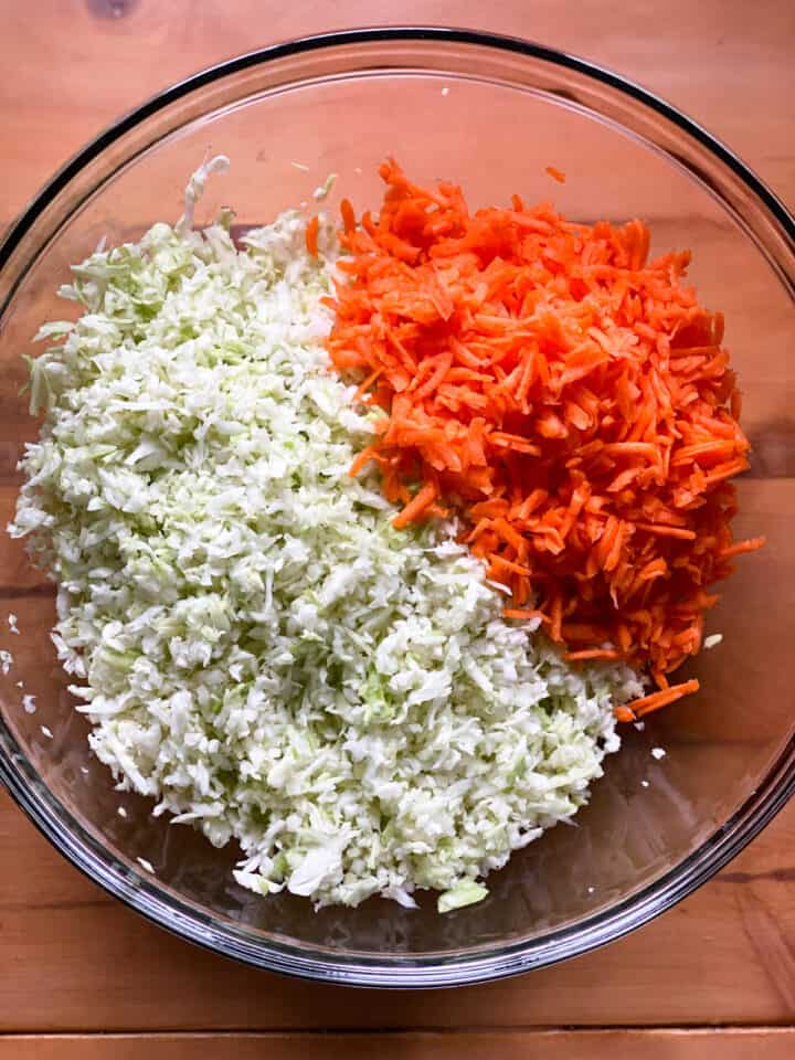 Shredded cabbage and shredded carrots in large glass bowl.