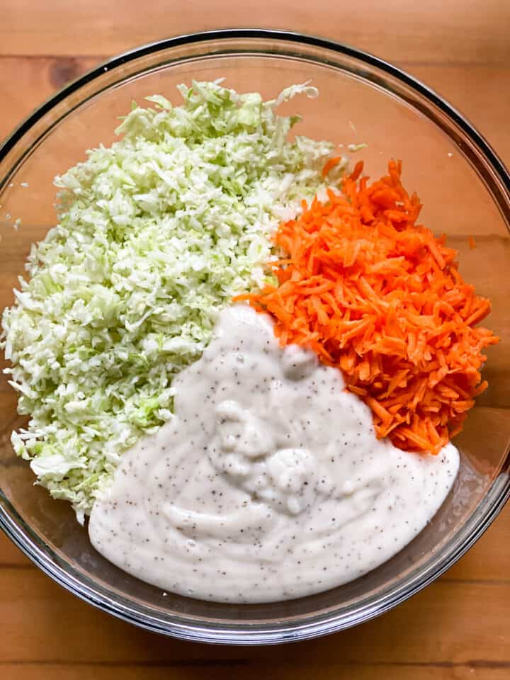 Dressing added to large glass bowl with the shredded cabbage and carrots.